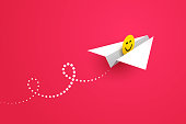 White paper airplane and yellow happy smiling face icon over red background. Concept of good news, sending greetings, wishing good mood, positive feedback and user experience