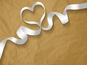 White pearl ribbon on a crumpled paper brown background.