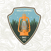 Wild camping patch. Vector. Concept for shirt, print, stamp, apparel or tee. Vintage typography design with camp lantern and forest silhouette. Outdoor adventure symbol