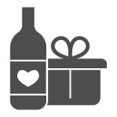 istock Wine Bottle And Gift Pack solid icon. Bottle with heart symbol and present with ribbon glyph style pictogram on white background. Winery signs for mobile concept and web design. Vector graphics. 1216982513