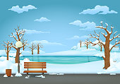Winter day park scene. Snow covered wooden bench with street lamp and trash can on an asphalt trail. Leafless trees, snow covered bushes on a snowy ground. Frozen lake on the background.