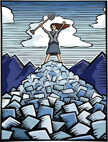 Woman standing on a pile of paperwork/bills holding a shovel triumphantly over her head.