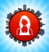 Woman Face on Rural Cityscape Skyline Background. The button is in the center of the illustration. a detailed 100% vector rural cityscape skyline is placed around the circumference of the button and includes various houses, single family homes, residential condominium and other suburb buildings. There is a blue sky background with a star burst glow rendered behind the buildings. The image is ideal for displaying rural suburban life concepts and ideas.