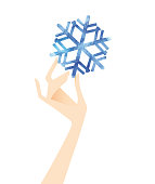 The illustration of a hand holding a watercolor snowflake on a white background