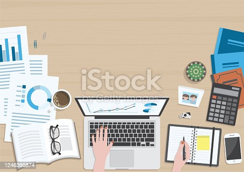istock Woman hands working on wood table top view 1246395874
