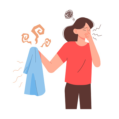 Woman holding sweaty smelly t-shirt and dislike.