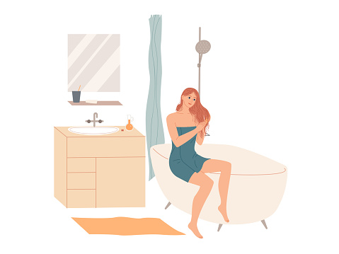 Woman in bath towel applies hair conditioner in bathroom after shower at home. Hair care