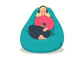 istock Woman in earphones sitting in comfortable bean bag 1187858547