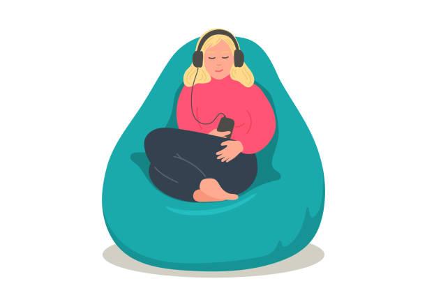 stockillustraties, clipart, cartoons en iconen met vrouw in oortelefoons zitten in comfortabele bean bag - alleen één jonge vrouw