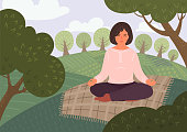 Woman meditates on meadow or in the park. Person sitting in lotus pose and meditating outdoors. Yoga, mindfulness, relax, calm, breathing exercises on nature.