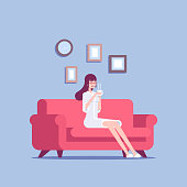 A young woman in a bathrobe sits on a sofa with a cup of coffee or tea in her hands. Smiling girl resting on couch after shower vector flat illustration