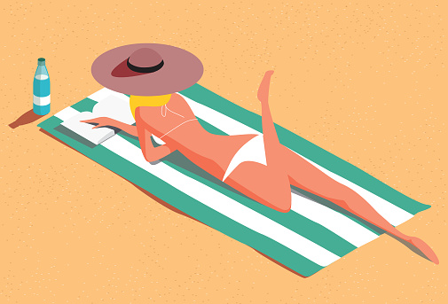 Woman on the beach sunbathing and reading