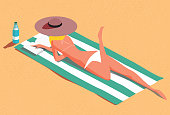 istock Woman on the beach sunbathing and reading 1266620343