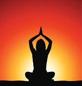 Woman perfoming yoga in front of sunrise