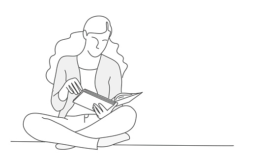 Woman sits in lotus position with book.