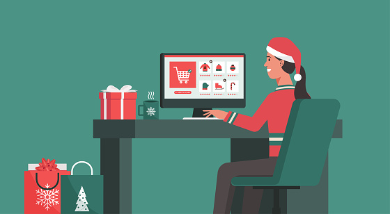 Woman sitting at the desk and making the order on a computer screen at his office on the Christmas holiday