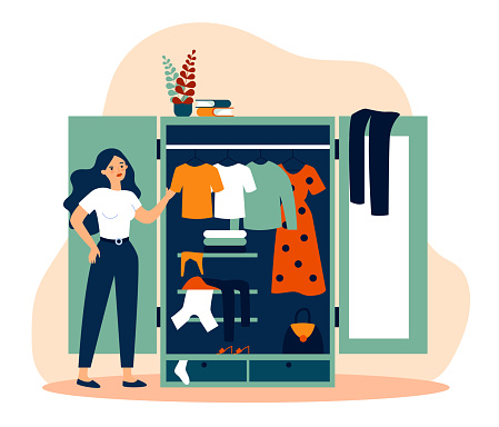 Woman standing near opened closet and looking at dresses