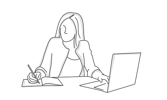 Woman using laptop and writing in a diary on her working desk.
