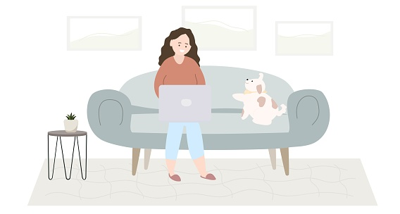 A woman with a laptop is sitting on a sofa with a dog. Home interior.