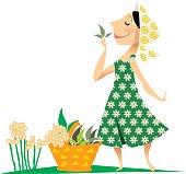 mujer con canasta con hierbas, aspirando el aroma de unas hojas