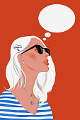 Woman dreaming isolated on a red background. Young girl is thinking. Portrait of lady with blond hair and sunglasses. Think dialog speech bubble.
