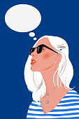 Woman dreaming isolated on a blue background. Young girl is thinking. Portrait of lady with blond hair and sunglasses. Think dialog speech bubble.