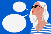 istock Woman with long blond hair wearing sunglasses and empty speech bubbles 1221656350