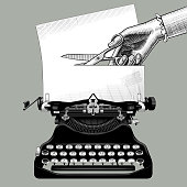 Woman's hand cutting a paper with scissors inserted into an old typewriter