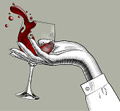 istock Woman's hand holding a glass with red splashed wine 1045327862