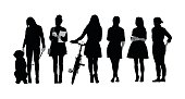 Silhouette vector illustration of a group of only young women.  One is standing with her dog, the other with a bicycle, one is holding her smartphone, and the others are standing in a row.