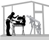 Residential construction with worker using a saw