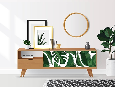 Wooden sideboard with plants and posters on it against white wall.