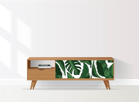Wooden sideboard with tropical pattern in living room.