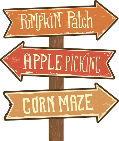 Wooden sign post with arrows pointing to Pumpkin Patch, Apple Picking and Corn Maze