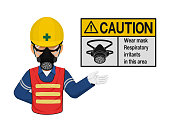 A worker with respiratory mask is presenting respiratory mask warning sign