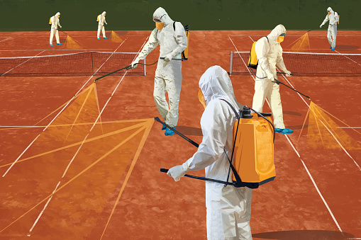 Workers in protective suits spraying tennis court
