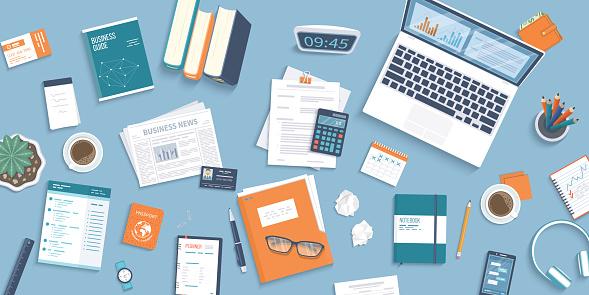 Workplace Desktop background. Top view of table, laptop, folder, documents, notepad, business card, purse, calendar, clock, books,coffee, passport, crumpled paper. Business background, organization