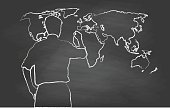 Chalk illustration on a black chalkboard of a world map and someone drawing information on top
