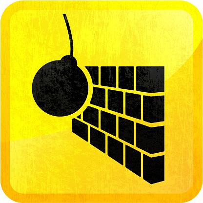 Wrecking ball smashing into brick wall on yellow background