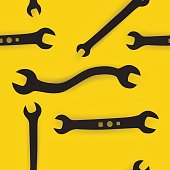 Wrenches and screw heads on yellow background seamless pattern