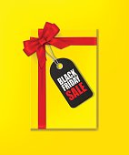 Yellow gift box with red ribbon and bow and tag with Black Friday Sale text on yellow background. Vector illustration.