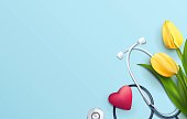 Yellow tulips and stethoscope on blue background. Top view. Happy nurse day concept. Vector illustration