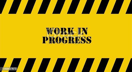 istock yellow warning sign. Work in progress background. 1253437873