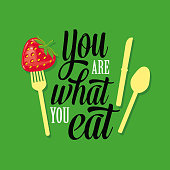 "Vector Illustration with a caption phrase typographic design ""You Are What You Eat"" with a fork holding a strawberry"