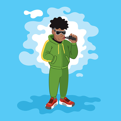 A young African American man standing in a cloud of steam and uses a vape in a cool tracksuit with a stylish hairstyle.