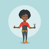 Young smiling african-american female repairman standing with a spanner in hand and giving thumb up. Repairman in overalls holding a spanner. Vector cartoon illustration. Square layout.