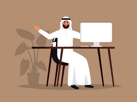 Young Arab man sitting at the table using the computer.