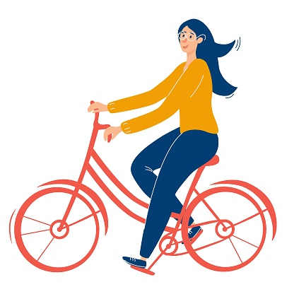 Young, beautiful girl with glasses rides a red bicycle. Girl healthy leisure rides bike side profile view.