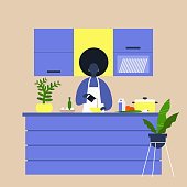 Young black female chief cooking food at the kitchen island table