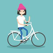 Young brunette girl riding a bike and waving her hand